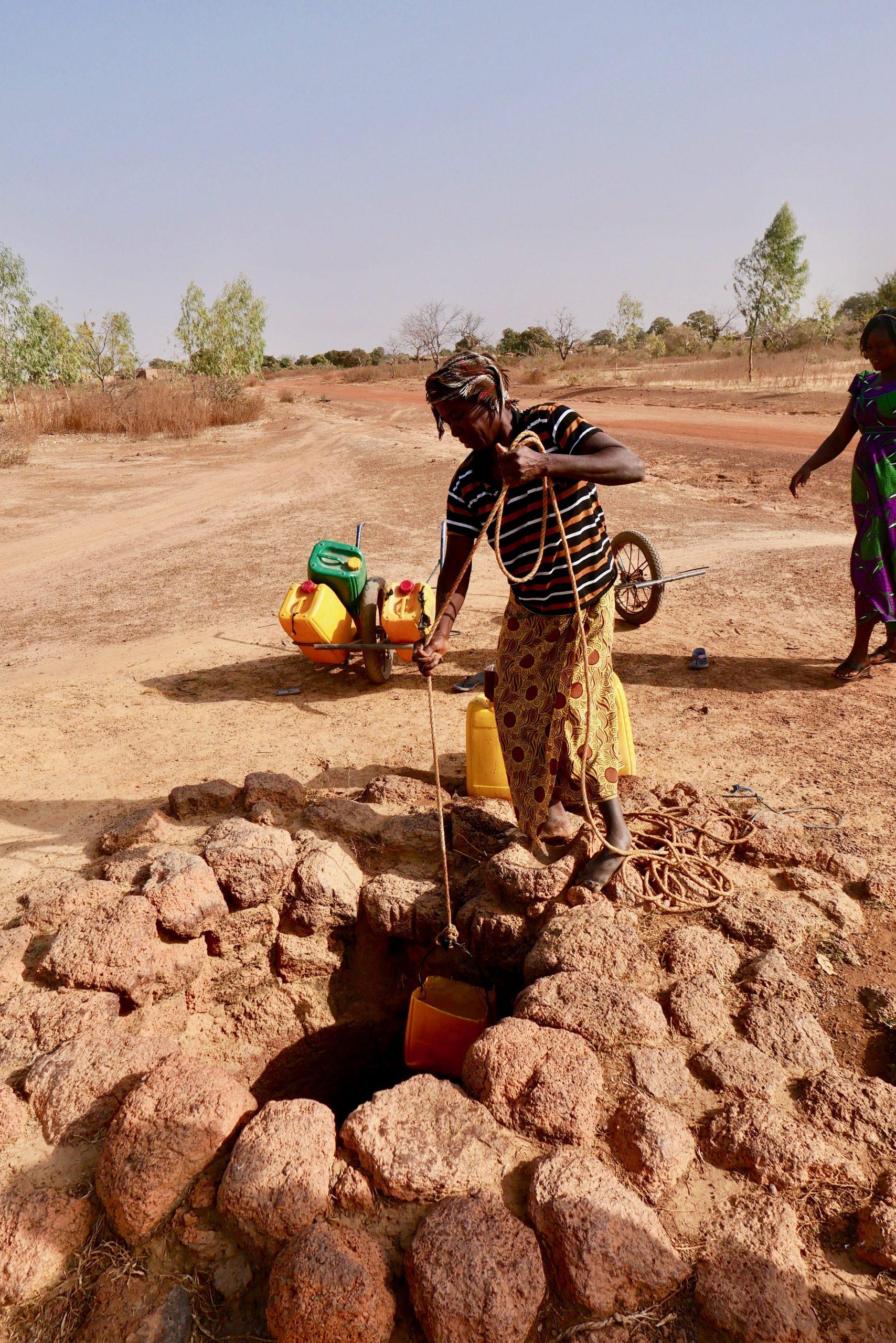 Barfuss schöpft eine Frau in ihren 60-iger Jahren Wasser für ihre Familie aus einem Brunnen